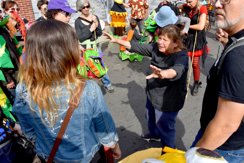 Sara Peattie advises those marching in the Honk Parade with the Puppeteers Cooperative before it begins, Oct. 13, 2019. (Greg Cook photo)