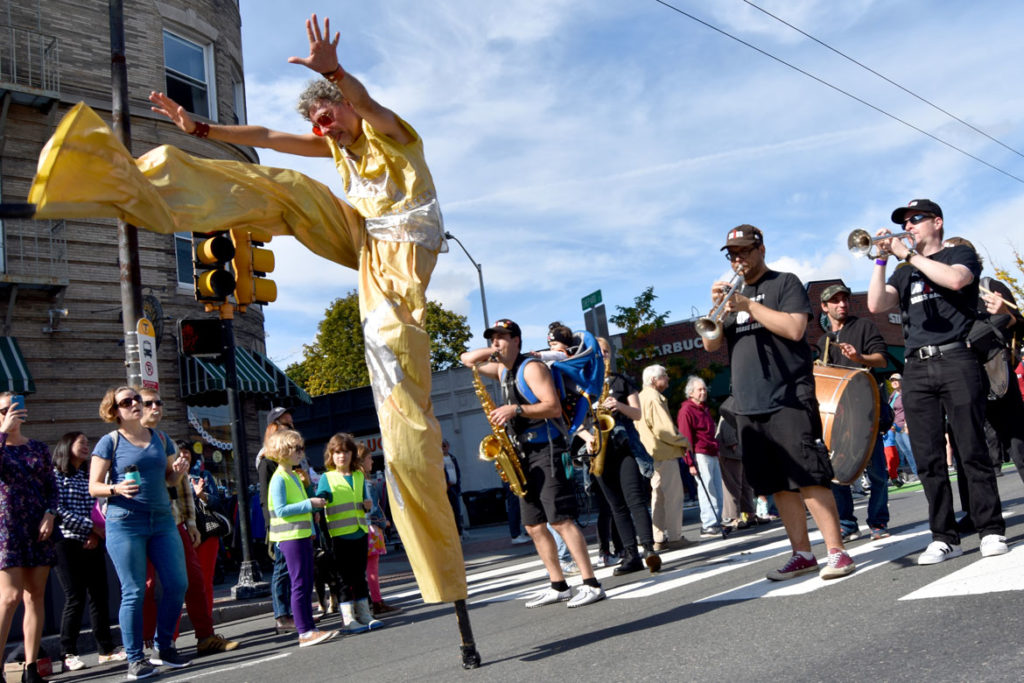 Stilter Shawn Morrisey dances in front of Boston's Dirty Water Brass Band during the Honk Parade, Oct. 13, 2019. (Greg Cook photo)