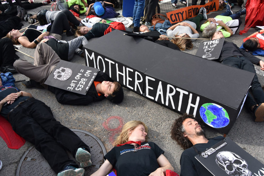 Extinction Rebellion die-in against global warming at Harvard Square, Cambridge, during in the Honk Parade, Oct. 13, 2019. (Greg Cook photo)