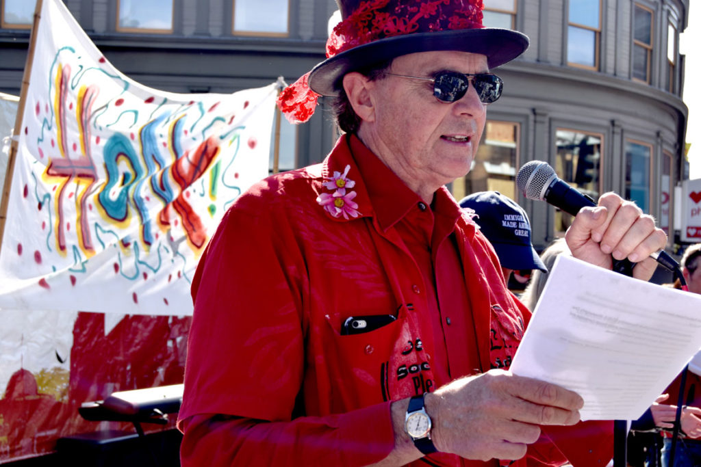 John Bell serves as MC at the main stage at Harvard Square, Cambridge, during the Honk Parade, Oct. 13, 2019. (Greg Cook photo)