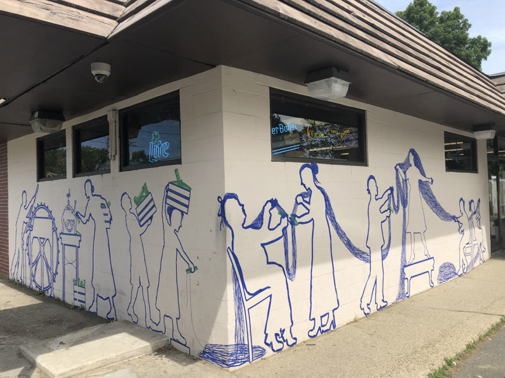 """Celebrating West Newbury's history of comb manufacturing with a Tape Art mural at the West Newbury Food Mart, July 2019. From """"Drawing From Our Past: A Tri-Town Tape Art Festival."""" (Tape Art photo)"""
