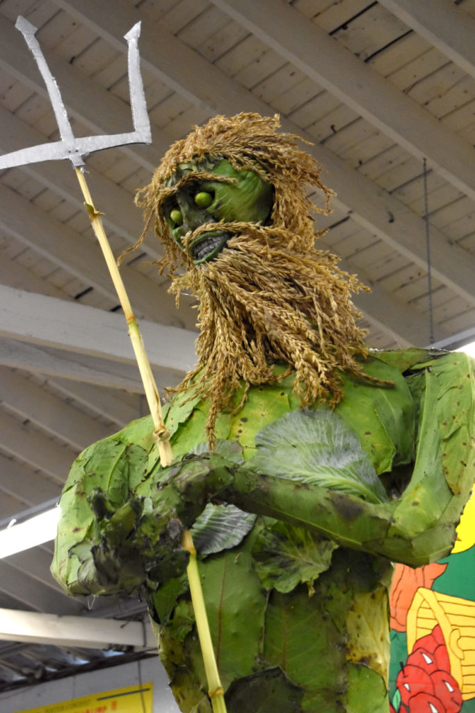 Poseidon scarecrow made by the Wong Family of Topsfield from wild rhubarb leaves, wild cucumber, leaves, burdock, phragmites, cabbage, corn, trumpet vine pods and artichoke. Inside the Fruits & Vegetables Barn at the Topsfield Fair, Oct. 6, 2019. (Greg Cook photo)