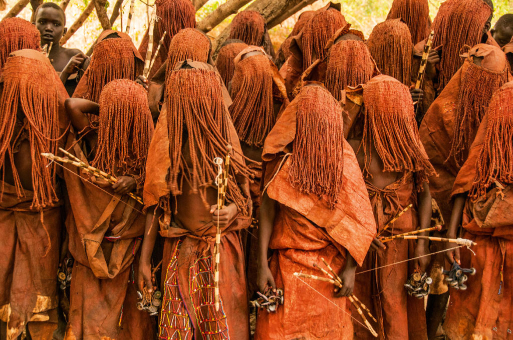 "The veiled Pokot boys in a remote northwestern Kenya, ""are in state of limbo in their transition to manhood. During this period, they travel through the forest in long lines singing songs to the sound of their shakers made of bottle tops and string,"" Carol Beckwith and Angela Fisher write in ""African Twilight: The Vanishing Rituals and Ceremonies of the African Continent,"" 2018. (Rizzoli)"
