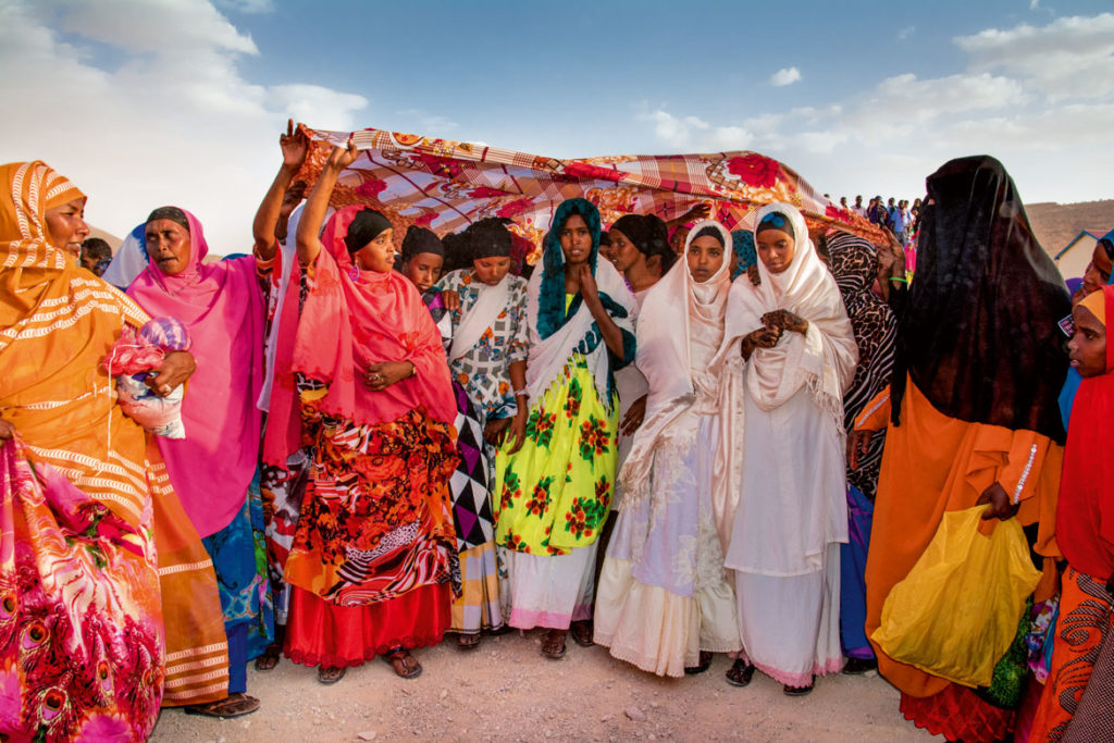 "A traditional Somali wedding: ""Dressed in white, the bride leaves her home under the protection of a colorful, handheld canopy and proceeds with female relatives to the aqal, the ritual wedding hut,"" Carol Beckwith and Angela Fisher write in ""African Twilight: The Vanishing Rituals and Ceremonies of the African Continent,"" 2018. (Rizzoli)"