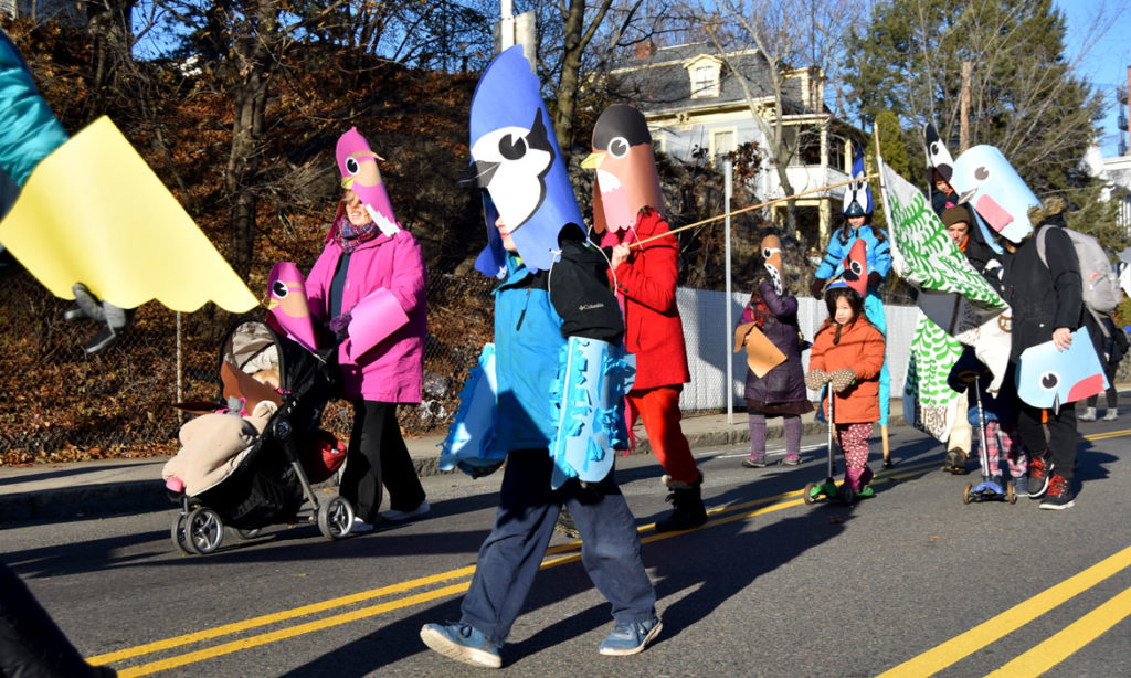 """Songbirds for Diversity"" by Wonderland Spectacle Co. and friends in Malden Parade of Holiday Traditions, Nov. 30, 2019. (Greg Cook photo)"