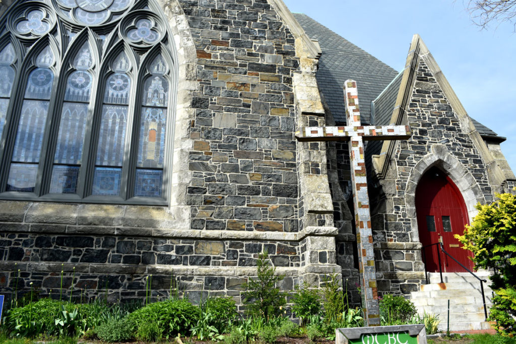 "Old Cambridge Baptist Church mass shootings cross: ""This cross is an evolving witness to the lives lost in 2018 due to mass shootings in the U.S. It is our sign of protest against the love of money and guns being valued over human lives. This death-dealing evil must end. Resurrection of peace and justice must persist."" May 9, 2019. (Greg Cook photo)"