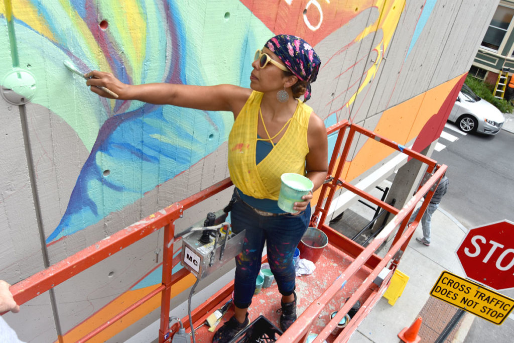Silvia López Chavez paints a mural on Cambridge's Central Square Library, Aug. 28, 2019. (Greg Cook photo)