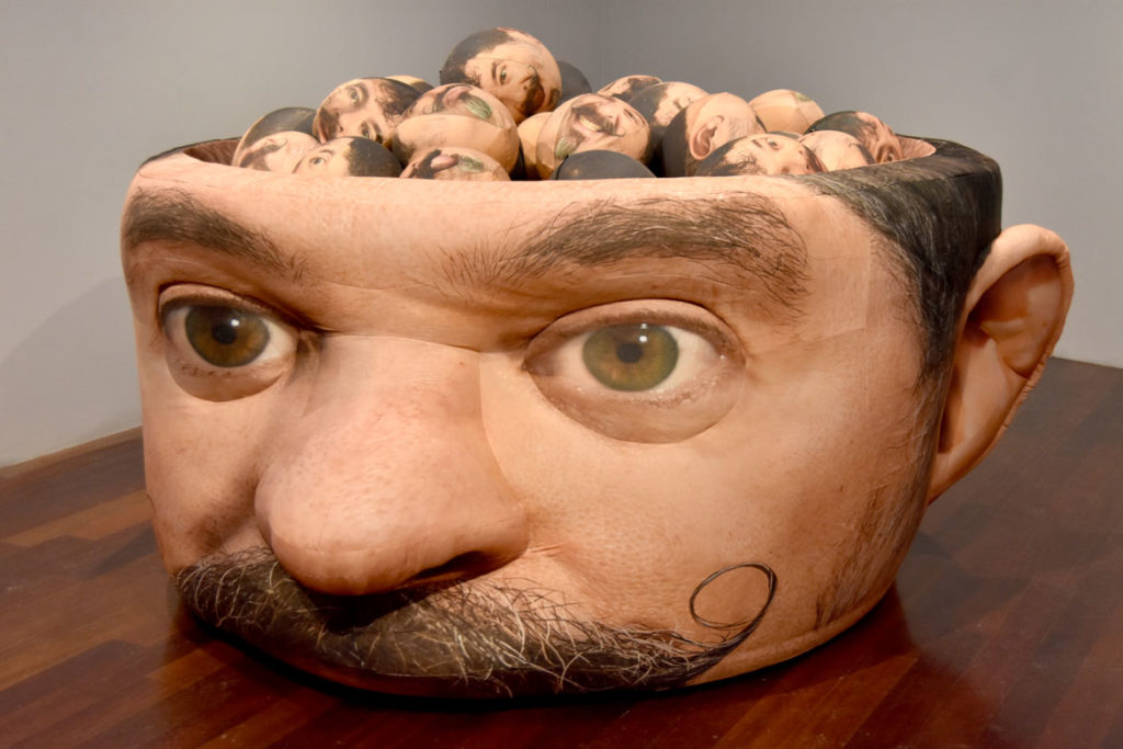 "Jeffu Warmouth, ""Urgent Blowout,"" 2019, 54-inch-tall, 120-inch long inflatable fabric sculpture filled with 36 inflatable heads, at Boston Sculptors Gallery, Boston, Dec. 13, 2019. (Greg Cook photo)"