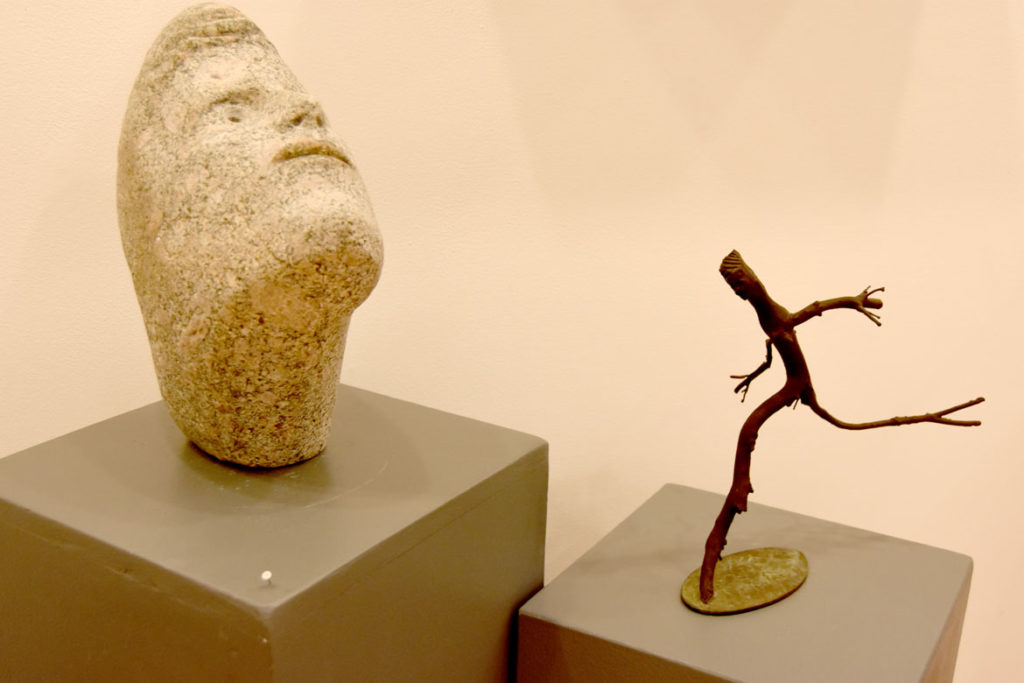 """Joseph Wheelwright, """"Gentle Stone,' 2014, carved stone (left), and """"Dancing Twig Person,"""" 2015, carved manzanita twigs from Tucson, Arizona. (Gallery Kayafas)"""