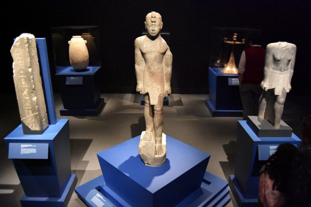 """A granite gneiss statue of Nubian King Senkamanisken (center), from his reign 643-623 BCE, found at Gebel Barkal, displayed with other Napatan period pieces. From """"Ancient Nubia Now"""" at Boston's Museum of Fine Arts, Jan. 15, 2020. (Greg Cook photo)"""