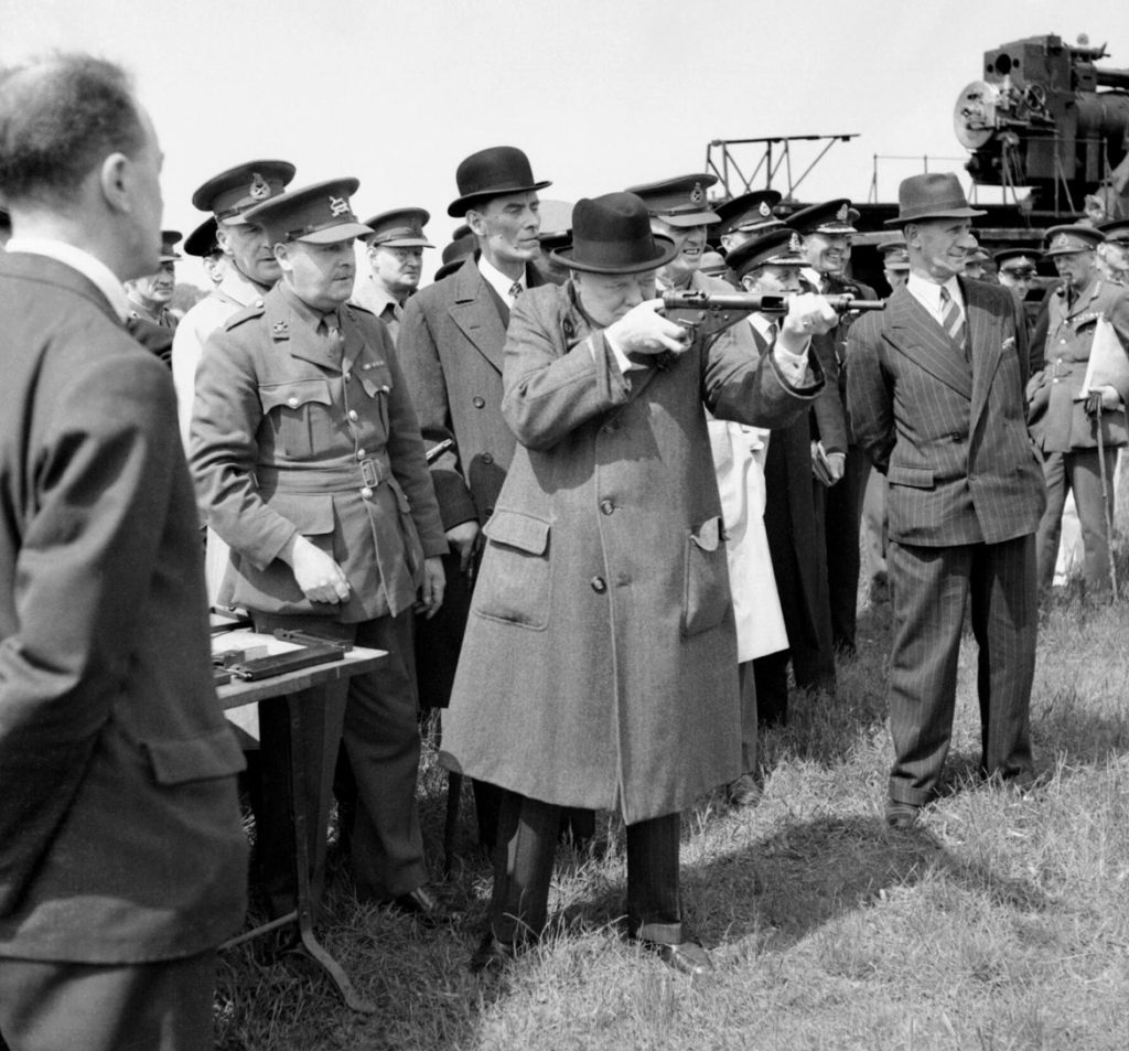 British Prime Minister Winston Churchill aims a Sten gun during a visit to the Royal Artillery experimental station at Shoeburyness in Essex, June 13, 1941. (Imperial War Museums / Public Domain)