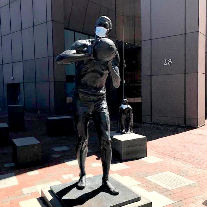 A protective mask has appeared on the 2013 statute of Boston Celtics star Bill Russell by by Ann Hirsch on Boston City Hall Plaza, c. April 6, 2020. (Courtesy)