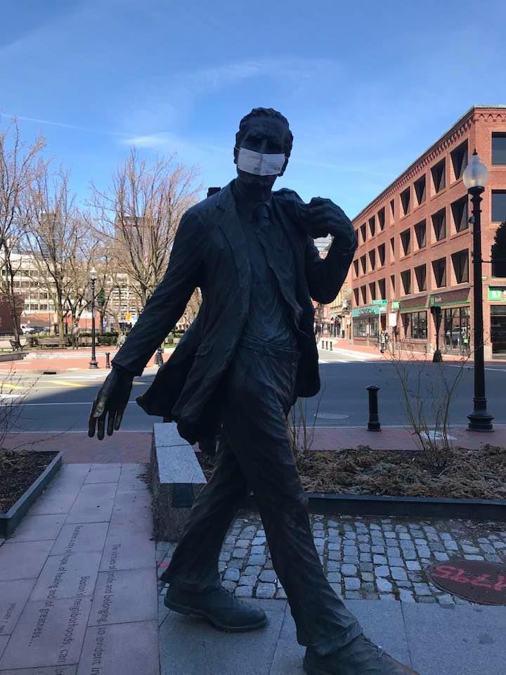 A protective mask has appeared on the statue of former Boston mayor Kevin White at Faneuil Hall, c. April 6, 2020. (Courtesy)
