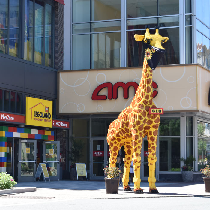 The Lego giraffe standing in front of Somerville's Legoland Discovery Center now wears a coronavirus mask, June 2020. (© Greg Cook photo)