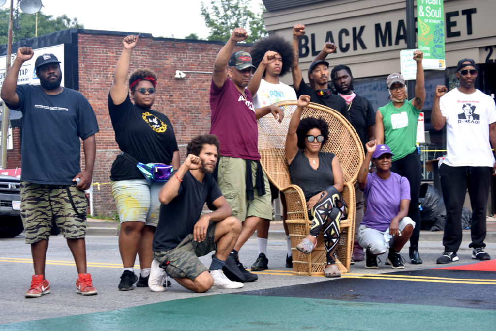 "The artists who painted the ""Black Lives Matter"" street mural on Washington Street in Boston's Nubian Square, surround Black Market owners Chris and Kai Grant (in chair), July 5, 2020. (© Greg Cook photo)"