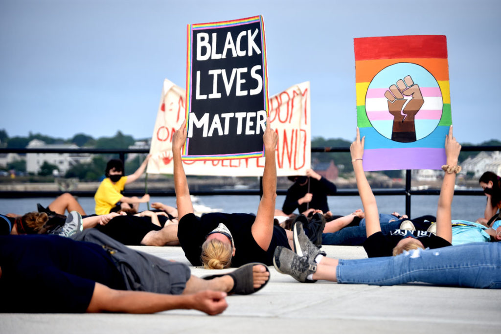 """Protesters lay in silence on the ground for 8 minutes and 46 seconds in memory of George Floyd during the """"Independence Day March"""" against injustice organized by Demilitarize Gloucester, July 4, 2020. (© Greg Cook photo)"""