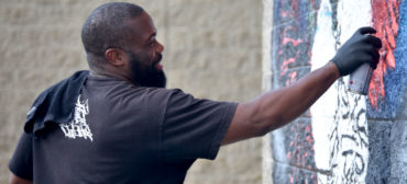 "Rob ""ProBlak"" Gibbs paints his ""Breathe Life"" mural at Boston's Madison Park Technical Vocational High School, July 5, 2020. (© Greg Cook photo)"