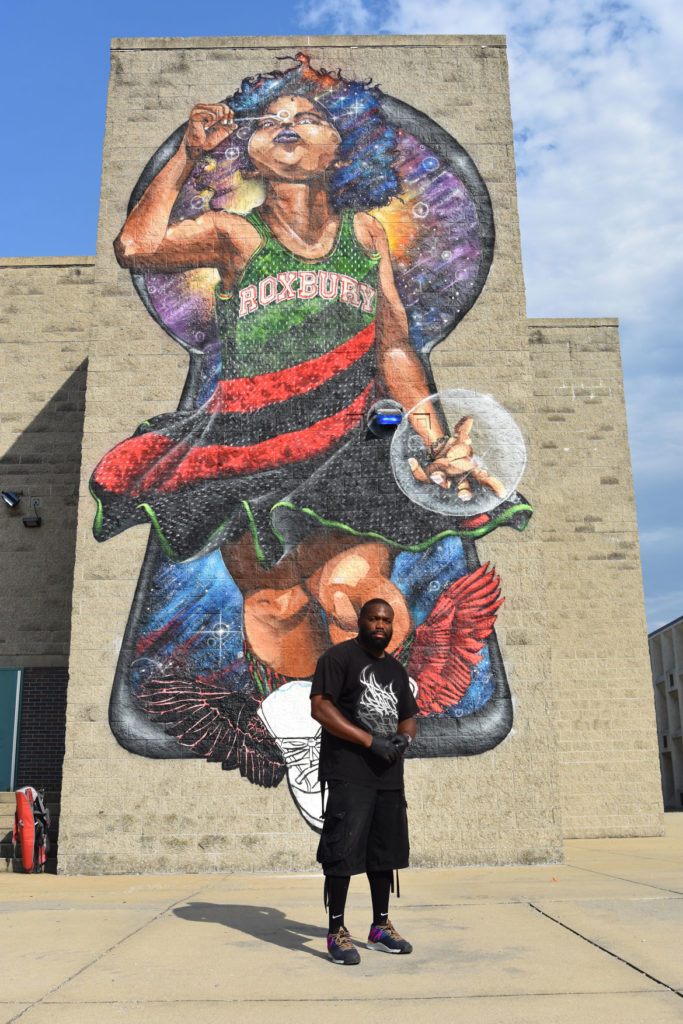 "Rob ""ProBlak"" Gibbs stands in front of his ""Breathe Life"" mural at Boston's Madison Park Technical Vocational High School, July 5, 2020. (© Greg Cook photo)"