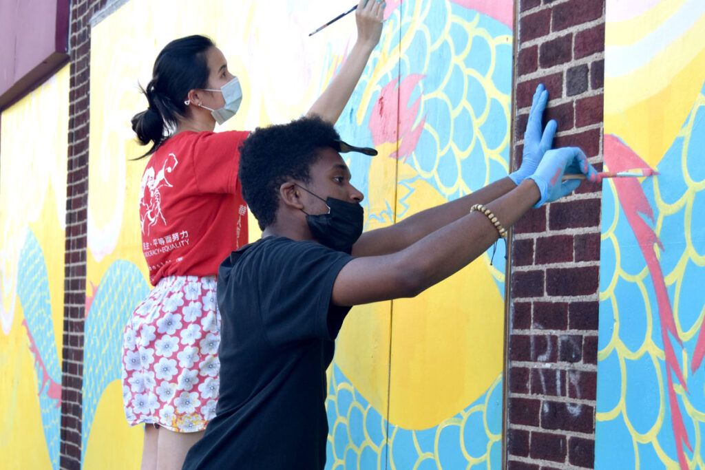 Jameson Francois (foreground) and Shaina Lu painting mural at Wah Lum Kung Fu & Thai Chi Academy in Malden, July 25, 2020. (Photo ©Greg Cook)