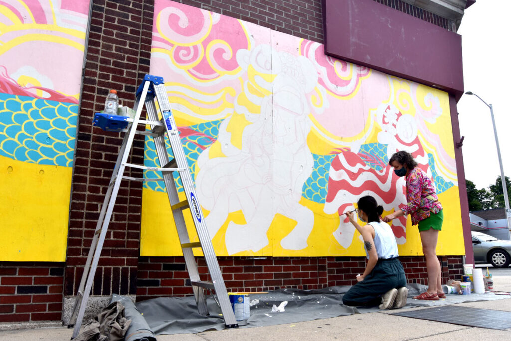 Shaina Lu (left) and Kari Percival painting mural at Wah Lum Kung Fu & Thai Chi Academy in Malden, July 29, 2020. (Photo ©Greg Cook)