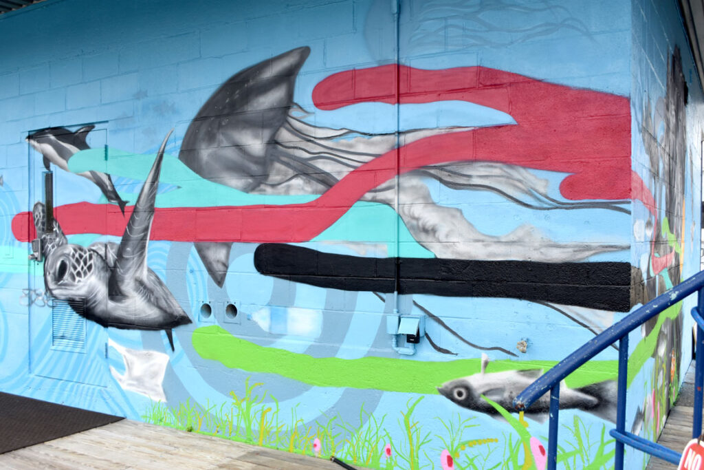 """Cedric """"Vise 1"""" Douglas and Julz Roth's mural for """"Sea Walls: Artists for Oceans, Boston 2020,""""from PangeaSeed Foundation in collaboration with HarborArts at the Boston Harbor Shipyard in East Boston, Sept. 18, 2020. (© Greg Cook photo)"""