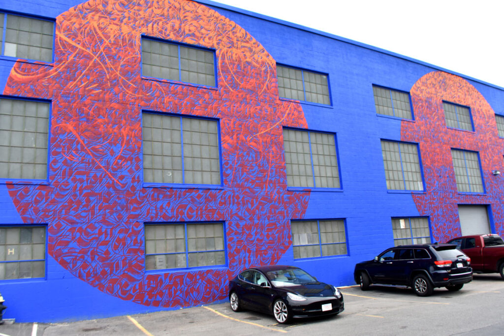 """Sneha """"Imagine"""" Shrestha's mural for """"Sea Walls: Artists for Oceans, Boston 2020,""""from PangeaSeed Foundation in collaboration with HarborArts at the Boston Harbor Shipyard in East Boston, Sept. 18, 2020. (© Greg Cook photo)"""