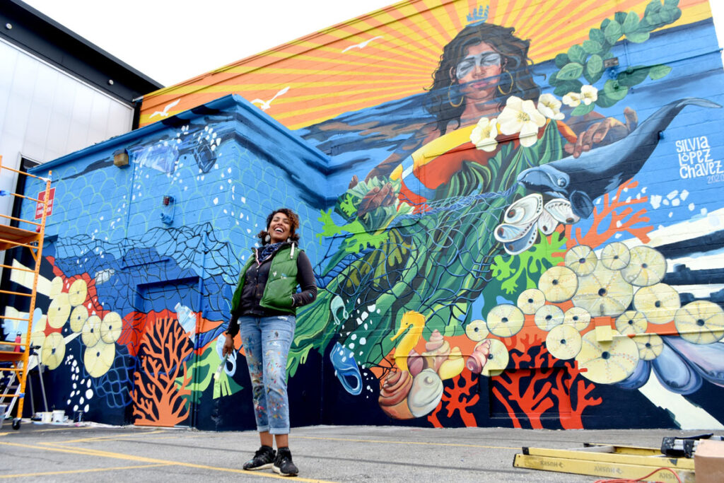 """Silvia Lopez Chavez with her mural for """"Sea Walls: Artists for Oceans, Boston 2020,""""from PangeaSeed Foundation in collaboration with HarborArts at the Boston Harbor Shipyard in East Boston, Sept. 18, 2020. (© Greg Cook photo)"""