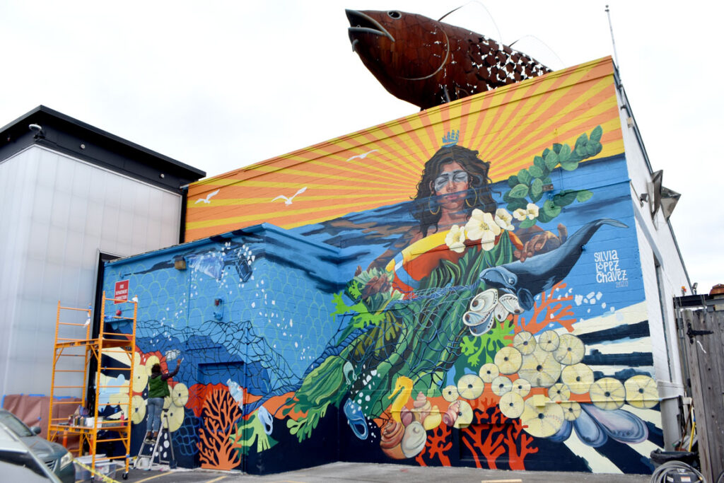 """Silvia Lopez Chavez painting her mural for """"Sea Walls: Artists for Oceans, Boston 2020,""""from PangeaSeed Foundation in collaboration with HarborArts at the Boston Harbor Shipyard in East Boston, Sept. 18, 2020. (© Greg Cook photo)"""