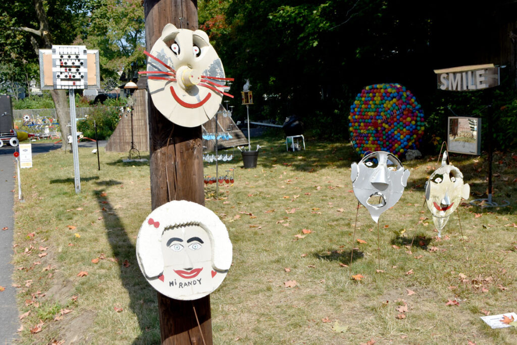 """Raymond Cardogno's """"Hubcap Faces"""" in """"Metal-ity"""" at ArtSpace Maynard, Sept. 25, 2020. (© Greg Cook photo)"""