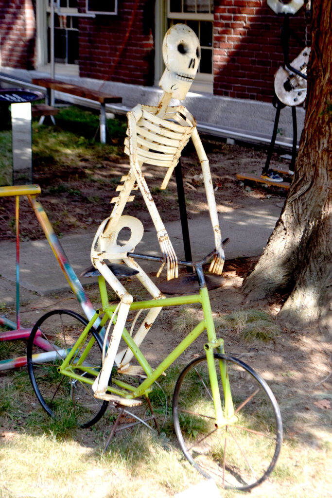 """""""Day of the Dead: Skeleton Bike Rider"""" by an unknown artist in """"Metal-ity"""" at ArtSpace Maynard, Sept. 25, 2020. (© Greg Cook photo)"""