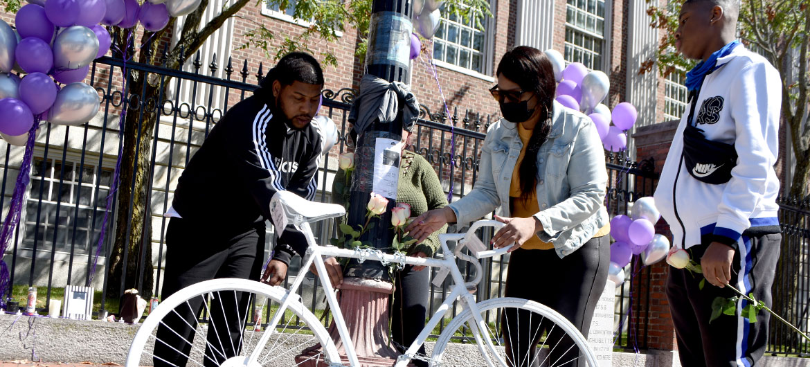 Family members of Darryl Willis, who was fatally struck by a truck in Cambridge's Harvard Square on Aug. 18, place flowers on a ghost bike set there in his memory on Sept. 19, 2020. (© Greg Cook photo)