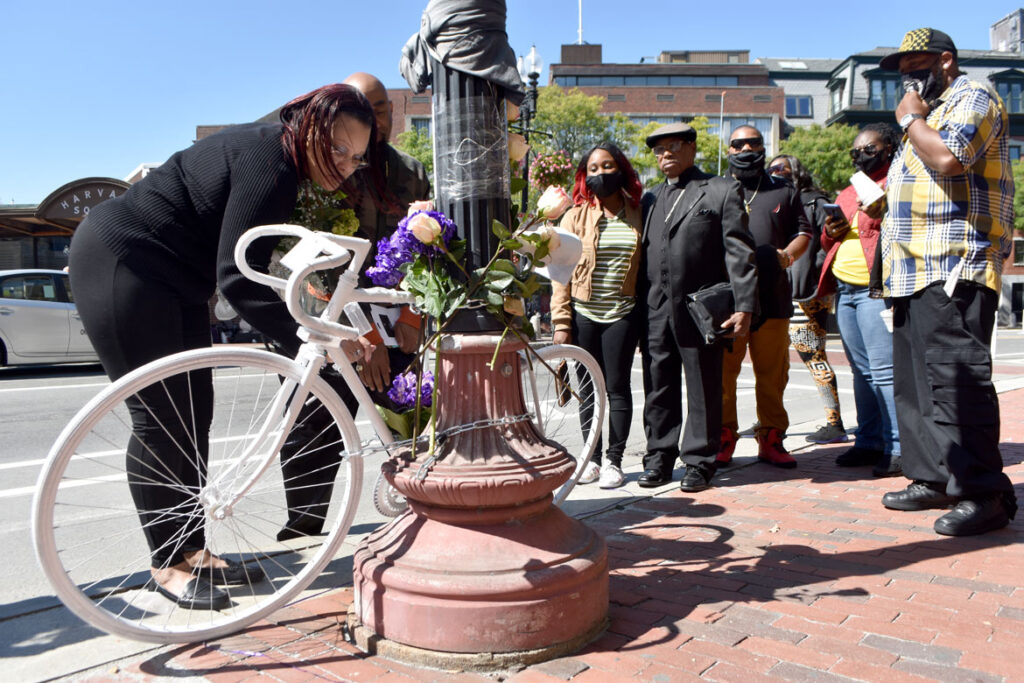 Donyell Chase-Willis (left) and other family members of Darryl Willis, who was fatally struck by a truck in Cambridge's Harvard Square on Aug. 18, place flowers on a ghost bike set there on Sept. 19, 2020. (© Greg Cook photo)