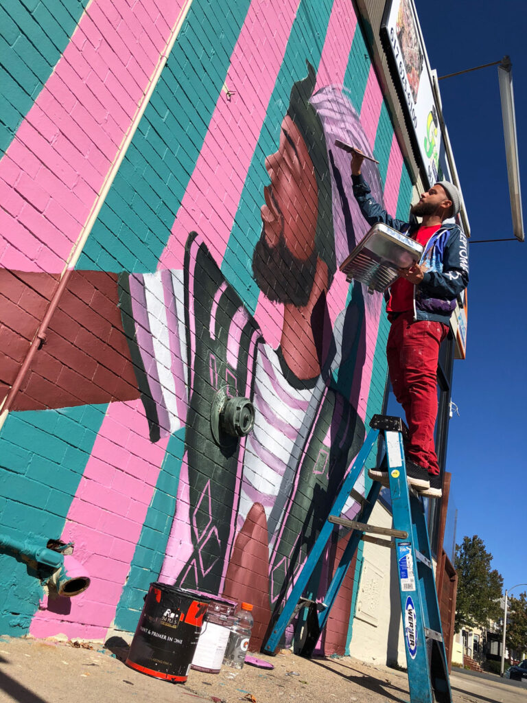 "Alexandre Keto paints his ""Doña Patria"" mural at 102 Broadway, Somerville, October 2020. (Photo by Iaritza Menjivar/Somerville Arts Council)"
