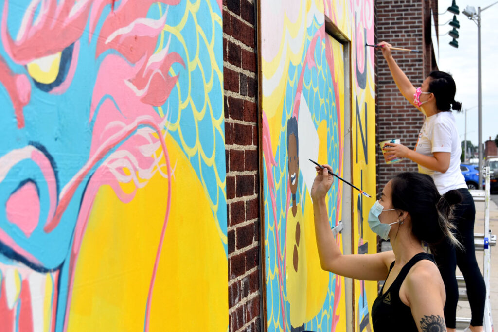 Shaina Lu (foreground) and Rayna Lo painting mural at Wah Lum Kung Fu & Thai Chi Academy in Malden, Aug. 8, 2020. (Photo ©Greg Cook)