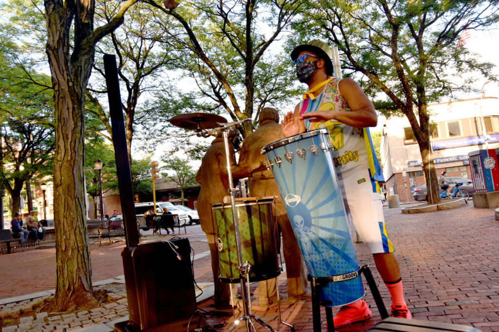 Marcus Santos of Grooversity drums in Somerville's Davis Square as part of a socially-distanced 2020 ArtBeat festival from the Somerville Arts Council, July 17, 2020. (©Greg Cook photo)