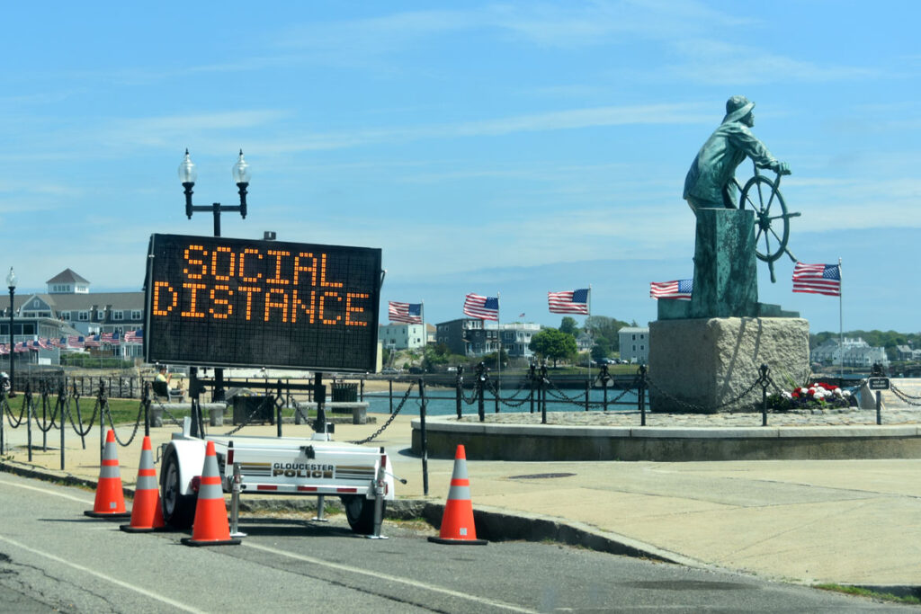 "A police sign at Gloucester's Fisherman statue warns to ""social distance,"" May 29, 2020. (©Greg Cook photo)"