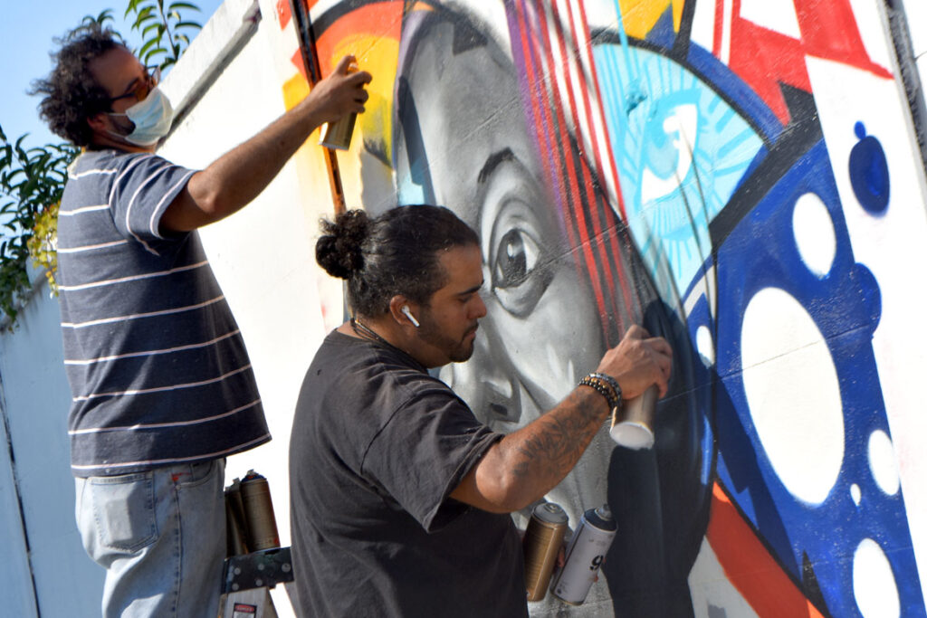 "Luis ""Take1"" Taforo (left) and Genaro ""GoFive"" Ortega paint a mural of singer Nina Simone at Salem's Punto Urban Art Museum, Oct. 11, 2020. (©Greg Cook photo)"