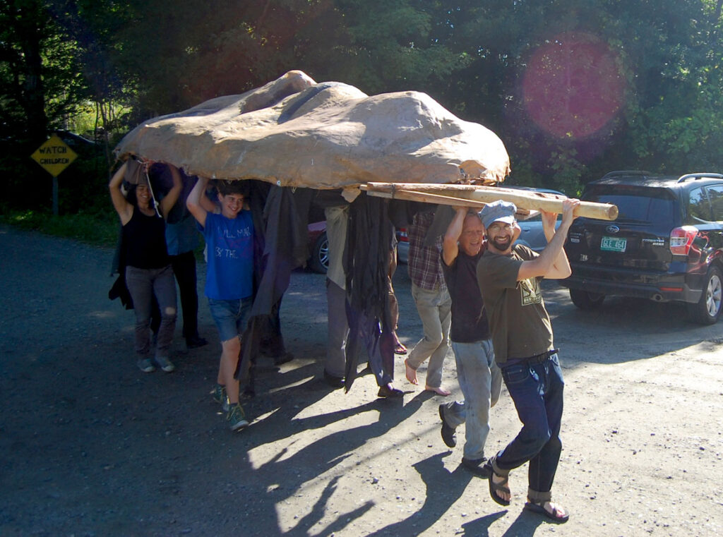 Remi Paillard (second from right) helps move the Mother Earth puppet head for the Bread and Puppet Pageant, Glover, Vermont, Aug. 22, 2015. (©Greg Cook photo)
