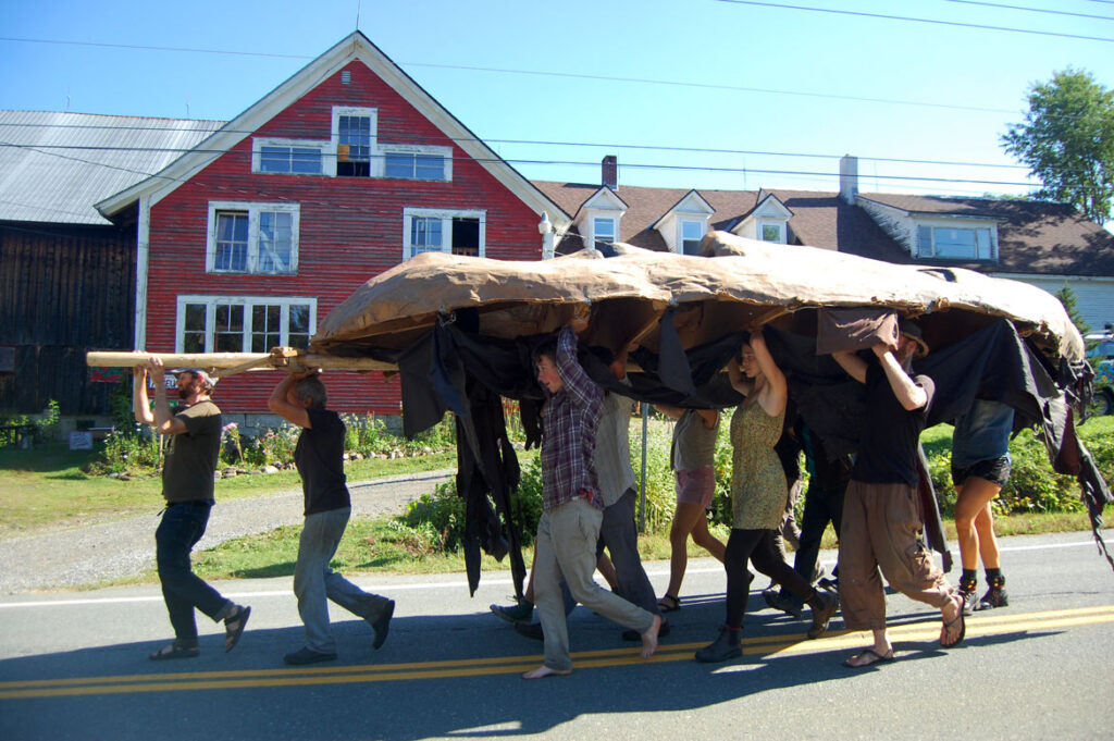Remi Paillard (second from left) helps move the Mother Earth puppet head for the Bread and Puppet Pageant, Glover, Vermont, Aug. 22, 2015. (©Greg Cook photo)