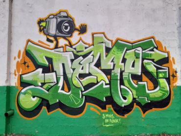 """Art by Deme5 created at the """"Back Against the Wall: Graffiti in Grove Hall"""" event at Moses Auto in Boston's Dorchester neighborhood on May 15, 2021. (Courtesy Sobek)"""