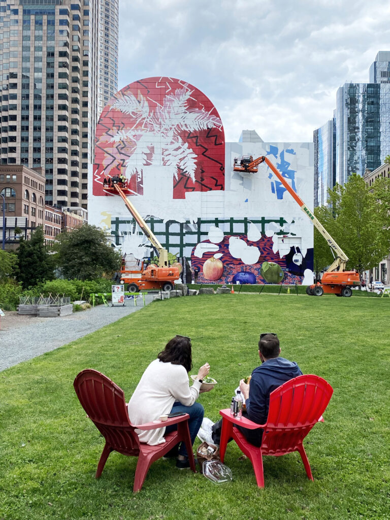 """The commercial painting firm Overall Murals works on """"Summer Still Life with Lobster and Fern,"""" designed by New York artist Daniel Gordon, on the tunnel ventilation building facing Dewey Square, along Purchase Street between Congress Street and Summer Street, May 2021. (Rose Kennedy Greenway Conservancy)"""