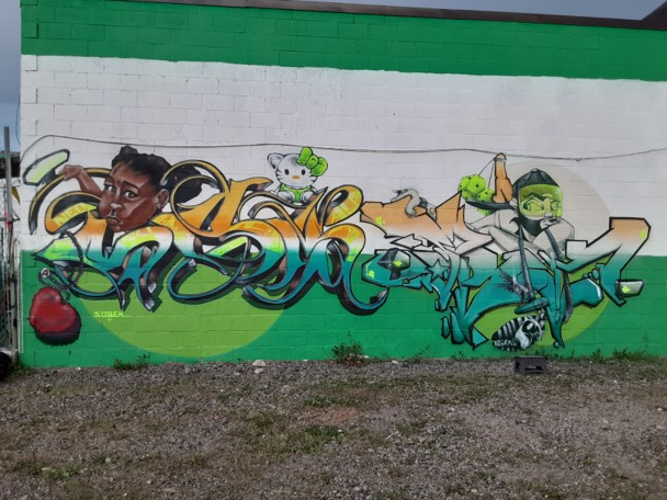 """Art by Sobek and ProBlak created at the """"Back Against the Wall: Graffiti in Grove Hall"""" event at Moses Auto in Boston's Dorchester neighborhood on May 15, 2021. (Courtesy Sobek)"""