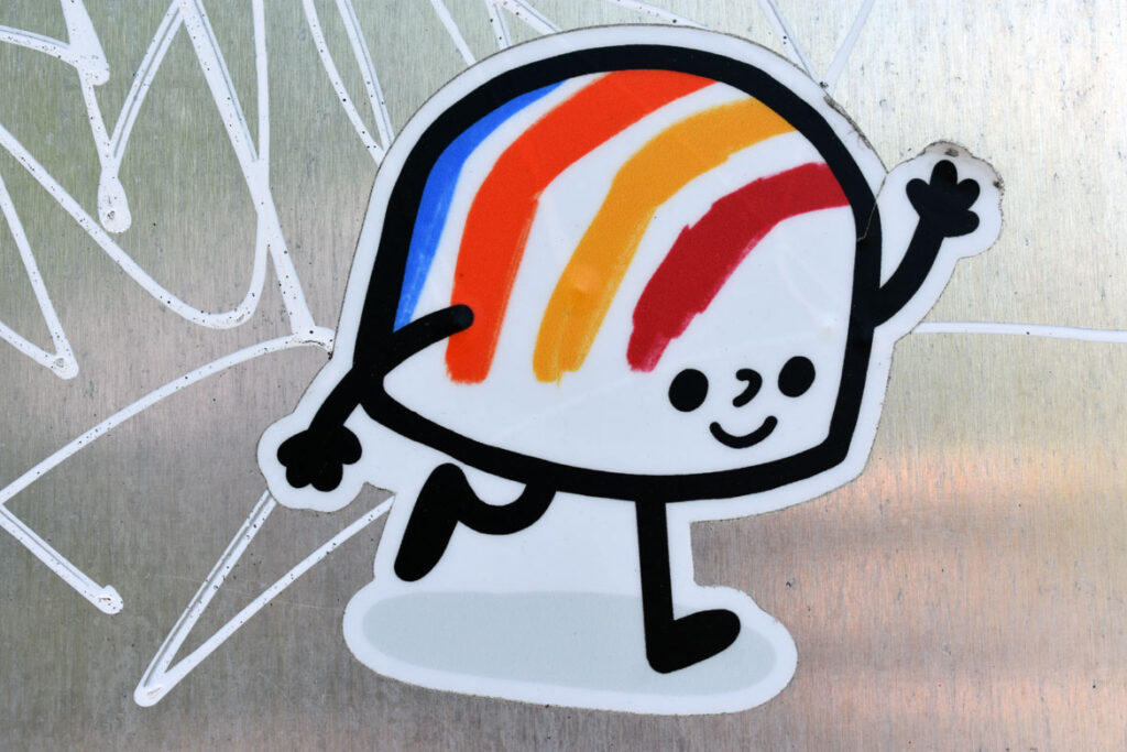 Street art sticker spotted on the back of a sign on Broadway by Cambridge's Sennot Park, riffing on Corita Kent's iconic 1971 rainbow gas tank design in Boston's Dorchester neighborhood. May 3, 2021. (©Greg Cook photo)