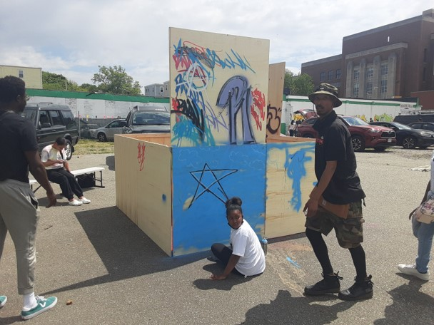 """""""Back Against the Wall: Graffiti in Grove Hall"""" event at Moses Auto in Boston's Dorchester neighborhood on May 15, 2021. (Courtesy Sobek)"""
