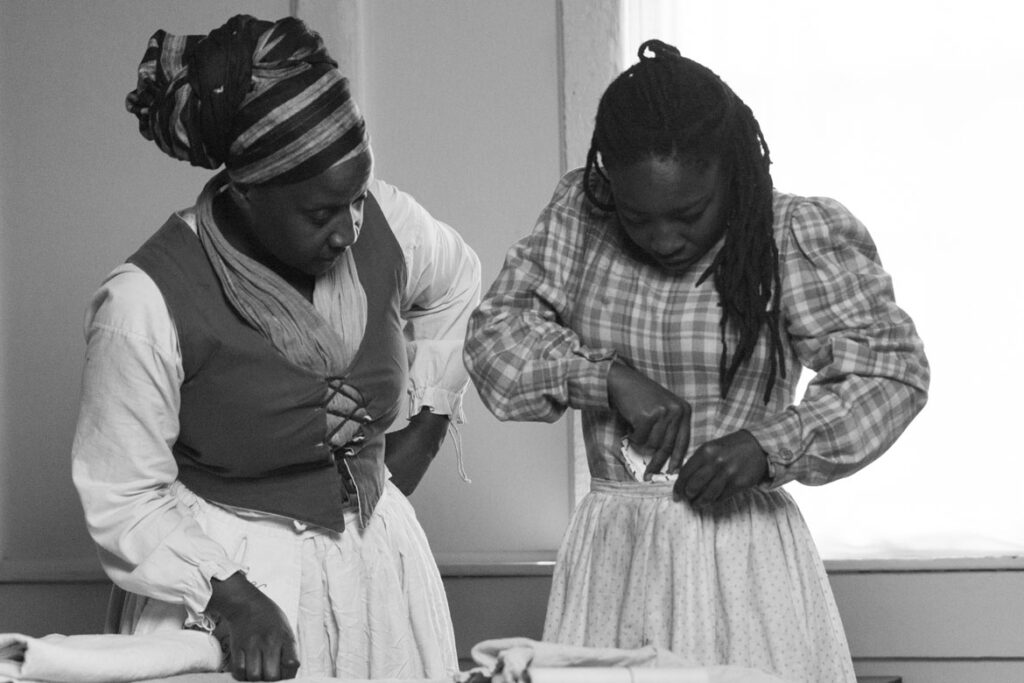 """In Ifé Franklin's 2021 film """"The Slave Narrative of Willie Mae,"""" Willie Mae (played by Qualina Lewis) hides a freedom map as her mother Virginia (Tammy Denease) watches. (Wayne Lake photo)"""