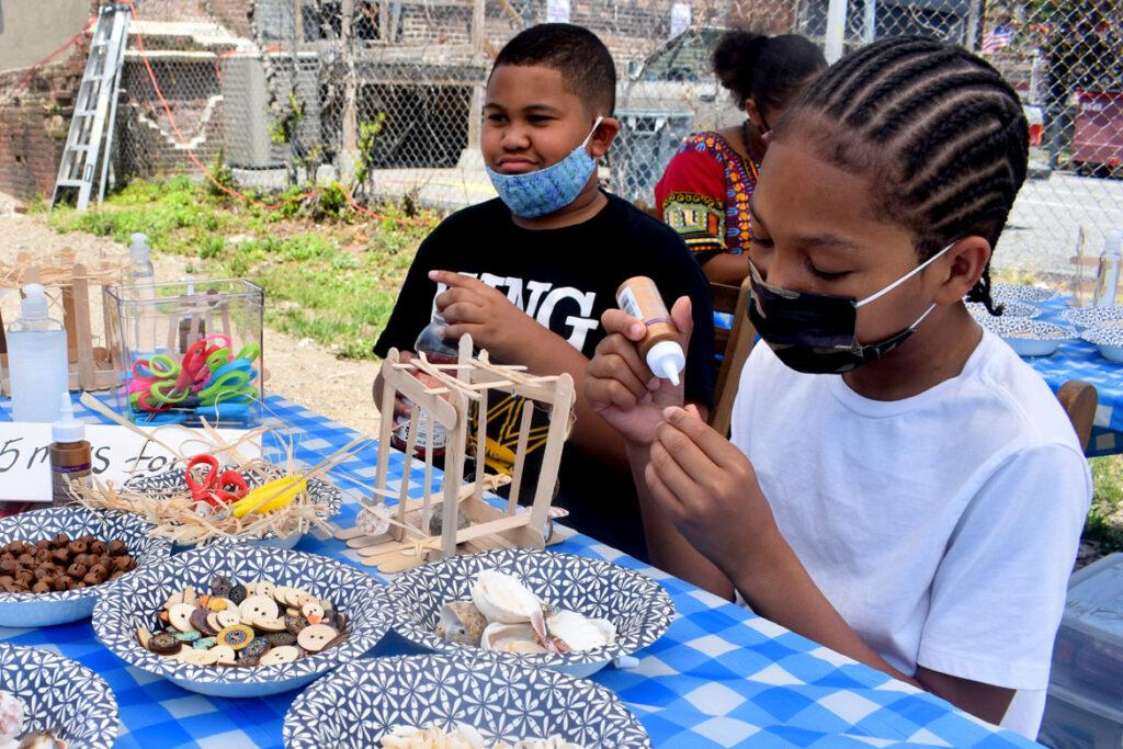 "Mini Ancestor Slave Cabin building workshop at Ife Franklin's Juneteenth Celebration at Black Market Nubian Square as part of the premiere of her film ""The Slave Narrative of Willie Mae,"" June 19, 2021. (©Greg Cook photo)"