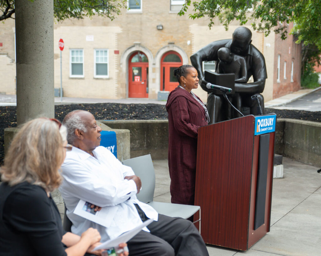 """Dr. Valerie Roberson, president of Roxbury Community College, speaks at the rededication of John Wilson's sculpture """"Father and Child Reading,"""" 1990, at the Boston school, July 13, 2021. (Courtesy Roxbury Community College)"""
