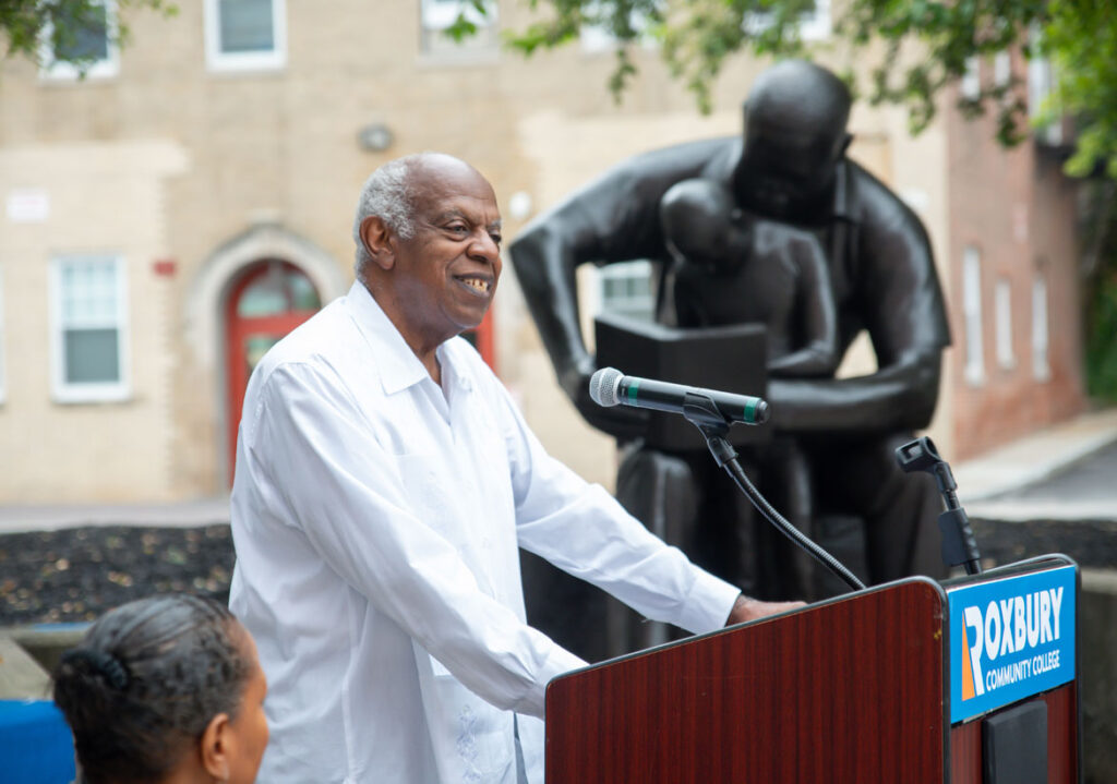 """Edmund Barry Gaither, director and curator of Boston's Museum of the National Center for Afro-American Artists, speaks at the rededication of John Wilson's sculpture """"Father and Child Reading,"""" 1990, at the Boston school, July 13, 2021. (Courtesy Roxbury Community College)"""