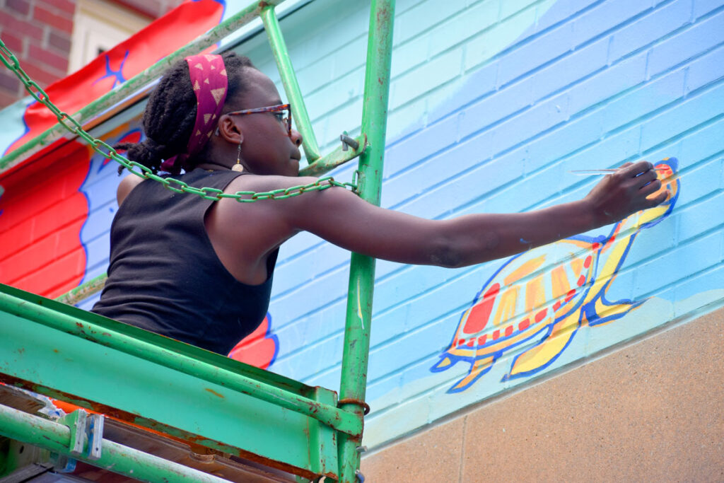 """Sabrina Dorsainvil of Boston paints at East Boston Early Education Center for the """"Sea Walls"""" mural project, July 23, 2021. (©Greg Cook photo)"""
