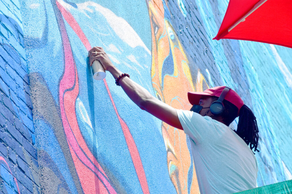 """Taj Francis of Jamaica paints at 150 Liverpool St., East Boston, for the """"Sea Walls"""" mural project, July 23, 2021. (©Greg Cook photo)"""